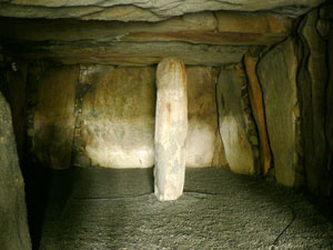 dark interior of a man-made stone cavern with a long standing stone rising from the floor